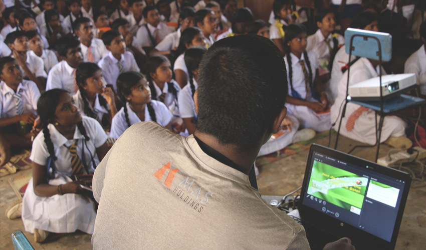 backshot of a person wearing mas t shirt doing a session to school children